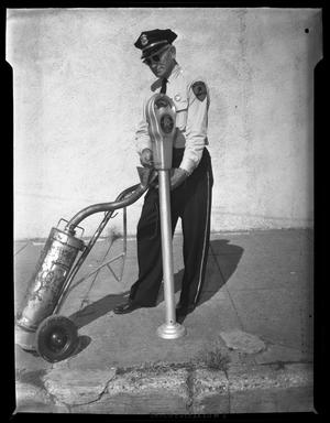 Primary view of object titled '[Denton police officer Carl Castleberry, emptying parking meter]'.
