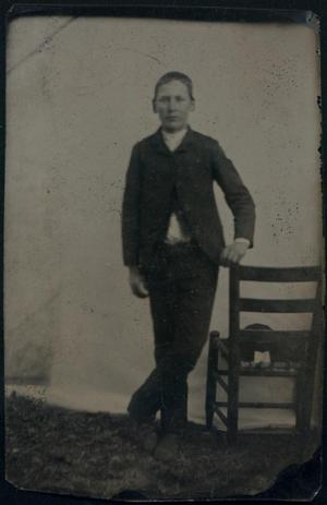 Primary view of object titled '[Boy Standing Next to Chair]'.