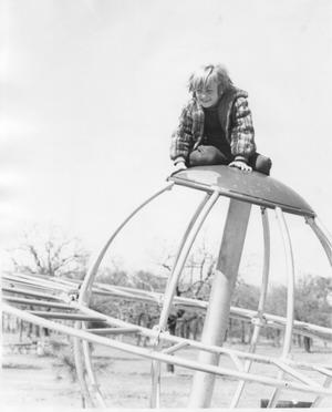Primary view of object titled 'Child Sitting on Top of Playground Equipment at Chisholm Park'.