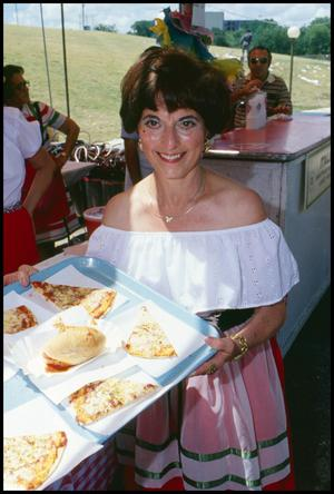 Primary view of object titled '[Woman Holding a Tray of Pizza Slices]'.
