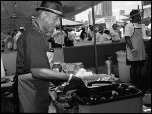 Primary view of object titled '[Man Cooking in Soul Food Booth]'.