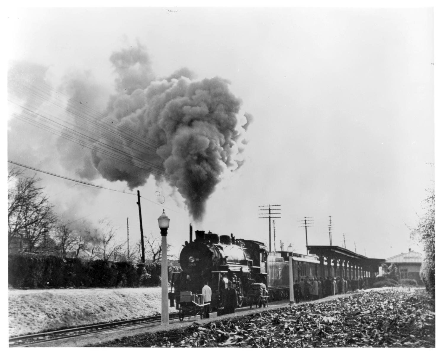 "[""Texas Special"" arriving at Highland Park Station], Missouri - Kansas - Texas (KATY) Railroads ""Texas Special"" train No. 2, northbound, headed by Engine No. 388, a Pacific type 4-6-2 locomotive, arriving at Highland Park station, enroute from the Dallas Union Station to St. Louis.,"