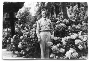 Primary view of object titled '[Buddy Sinclair in uniform by flower bush]'.