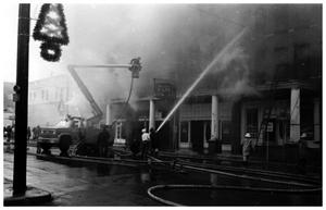 Primary view of object titled '[The Damron Hotel Fire, 12 of 21:   Numerous Fire Hoses Lying in Front of the Hotel]'.