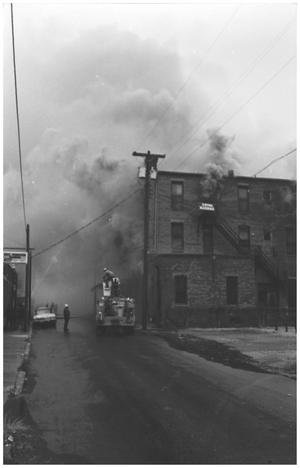 Primary view of object titled '[The Damron Hotel Fire, 9 of 21:   Firemen and a Fire Truck Near the North Side of Budiling]'.