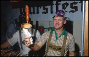 Primary view of object titled '[Bob Goebel Serving German Sausage on a Stick]'.