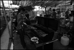 Primary view of object titled '[Woman Preparing Yakitori in Japanese Booth]'.