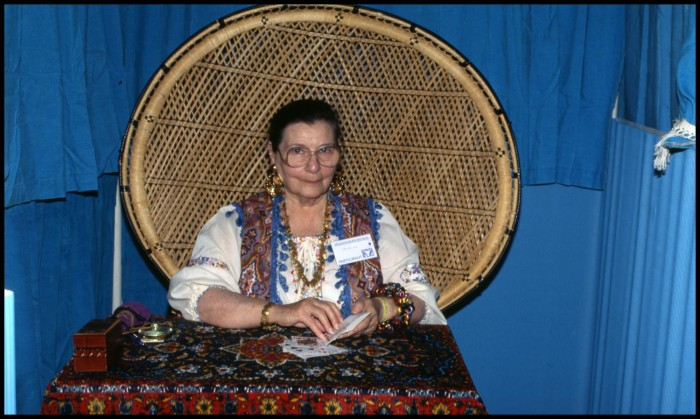 Photograph of the Blue Lady at the Texas Folklife Festival in San Antonio, Texas. In the photograph, the Blue Lady sits in a booth fashioned out of blue material. She wears a patterned vest, large glasses, dangling jewelry, and white blouse. In her hands she holds a pack of tarot cards. Her chair has a large, round back and is made out of bamboo.