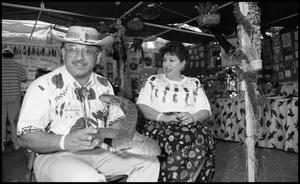 Primary view of object titled '[Eliseo and Nieves Torres at Mexican Folk Medicine and Folk Beliefs Booth]'.