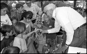 Primary view of object titled '[Jim Braud Shows Crawfish to Visitors]'.