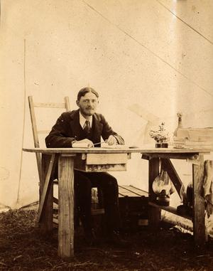 Primary view of object titled 'J. O. Schulze at Desk in Tent, c. 1902'.