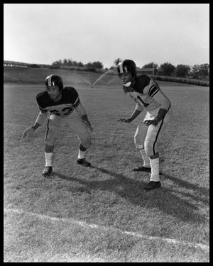 Primary view of object titled '[Two Football Players Standing in Athletic Stances]'.