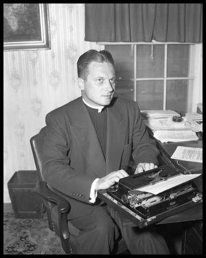 Primary view of object titled '[Photograph of a Priest in an Office]'.