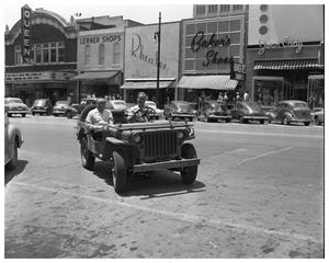 Primary view of object titled 'Two men in jeep on Congrees ave. near Queen Theatre'.