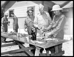 Primary view of object titled 'Soldiers making explosives with nails and cans'.