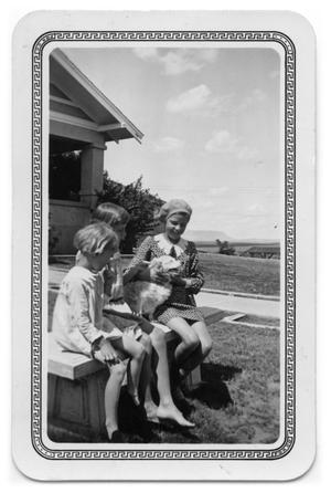 Primary view of object titled 'Girls sitting on a bench with a dog'.