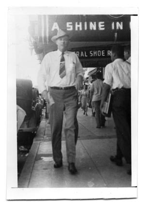 Primary view of object titled 'Unknown man walking down a sidewalk.'.
