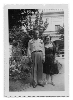 Primary view of object titled '[Marie Burkhalter stands with a man on a walkway]'.