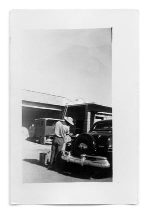 Primary view of object titled 'A 1948 Lincoln Continental being filled with gas'.