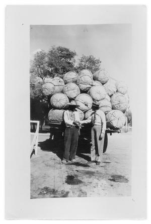Primary view of object titled 'Two unidentied man stand behind a truck with baskets'.