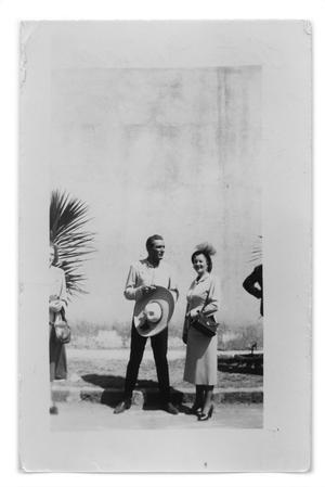Primary view of object titled 'Tito Guizar and Marie Burkhalter standing next to a sidewalk'.