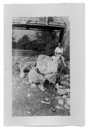 Primary view of object titled 'Marie Burkhalter on a pile of rocks under a railroad bridge'.