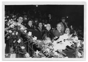 Primary view of object titled 'Marie Burkhalter sitting with a group of people in an audience'.