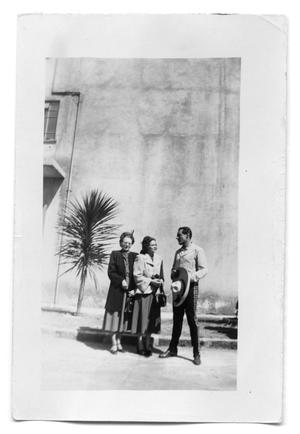 Primary view of object titled 'Man and two women outside a building'.