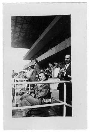 Primary view of object titled 'Woman sitting in stands in an arena'.
