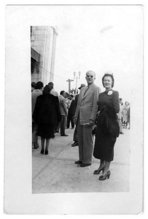 Primary view of object titled 'Couple stands on a sidewalk'.