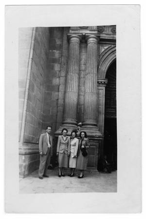 Primary view of object titled 'Unidentified group of people stand in front of a stone building'.