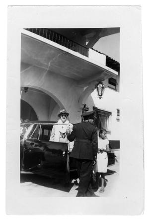 Primary view of object titled 'Unidentified man standing next a car'.