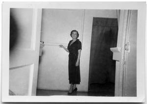 Primary view of object titled 'Woman standing in a hallway.'.