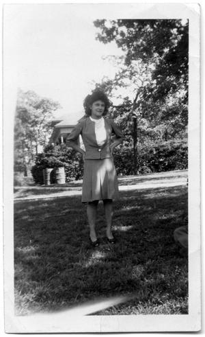 Primary view of object titled 'Woman standing in a field next to a sidewalk'.