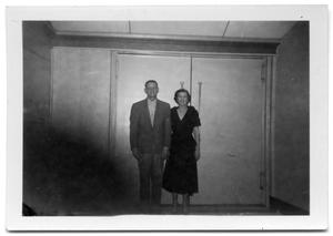 A man and woman standing in front of a pair of double doors