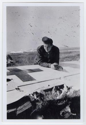 Primary view of object titled '[Photograph of Bill Bondurant Looking at Damage to Wing]'.