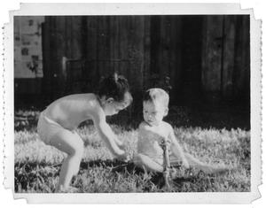 Primary view of object titled 'Ray Delphenis and another child playing with sprinklers'.