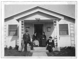 Primary view of object titled 'Four people at the entrance to a house'.