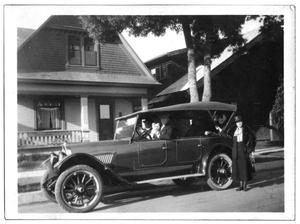 People inside a 1921 Oldsmobile parked outside a house