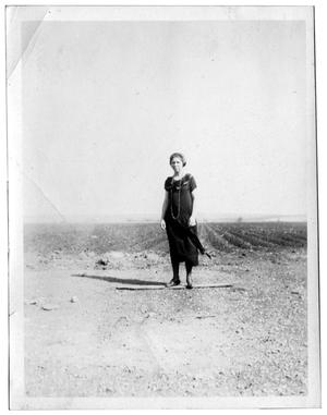 Woman standing in front of a crop field