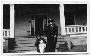Primary view of object titled 'Two women and a child in front of the steps to a house'.
