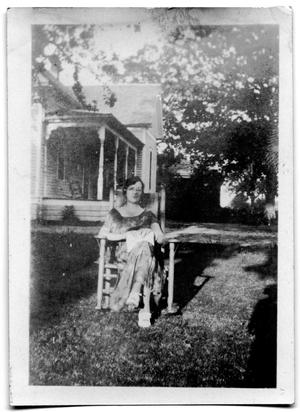 Primary view of object titled 'Woman sitting in a chair in the yard of a house'.