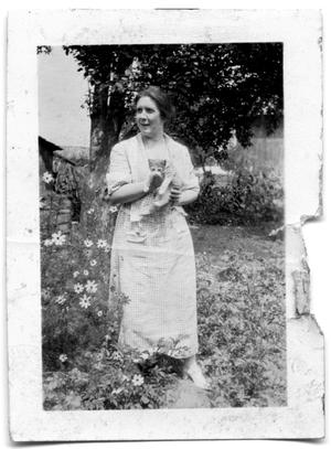 Primary view of object titled 'Woman holding a kitten in a garden'.