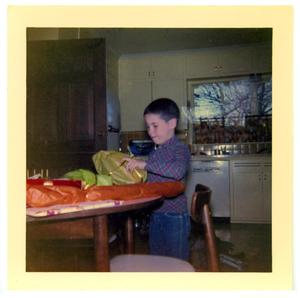 Primary view of object titled 'Boy at a table opening a package'.