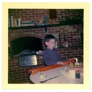Primary view of object titled 'Boy at a table with a wrapped package'.