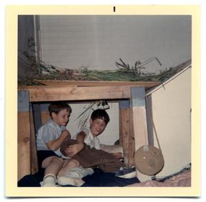 Primary view of object titled 'Two boys lying under a table arranging a blanket'.
