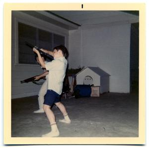 Primary view of object titled 'Boys playing with toy guns outside a home'.