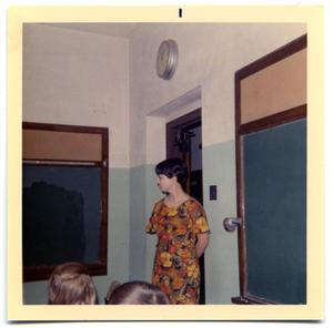 Primary view of object titled 'A gradeschool teacher standing next the entrance to a room'.