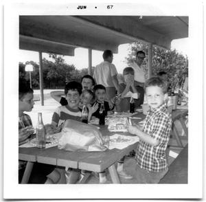 Primary view of object titled 'Group of school boys sitting at a picnic table'.
