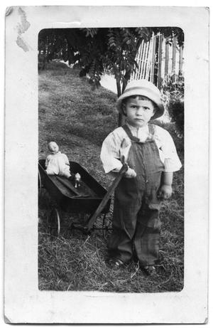 Primary view of object titled 'Postcard of boy pulling a wagon with toys'.